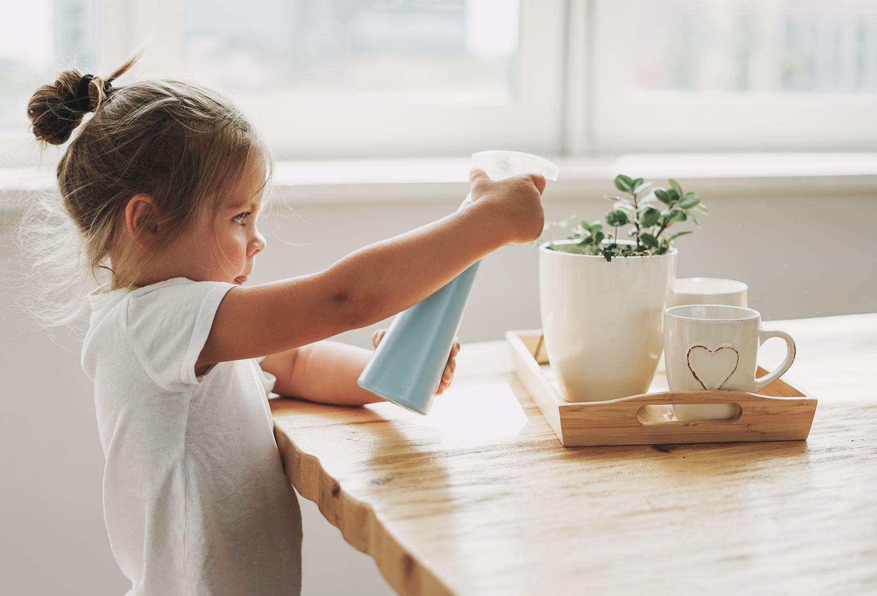 niña regando planta