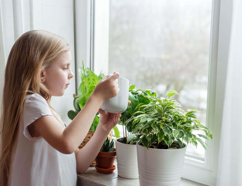 niña regando planta como parte del aprendizaje de vida practica montessori