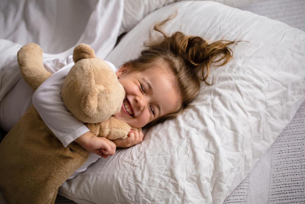 niña feliz en cama abrazando a un peluche