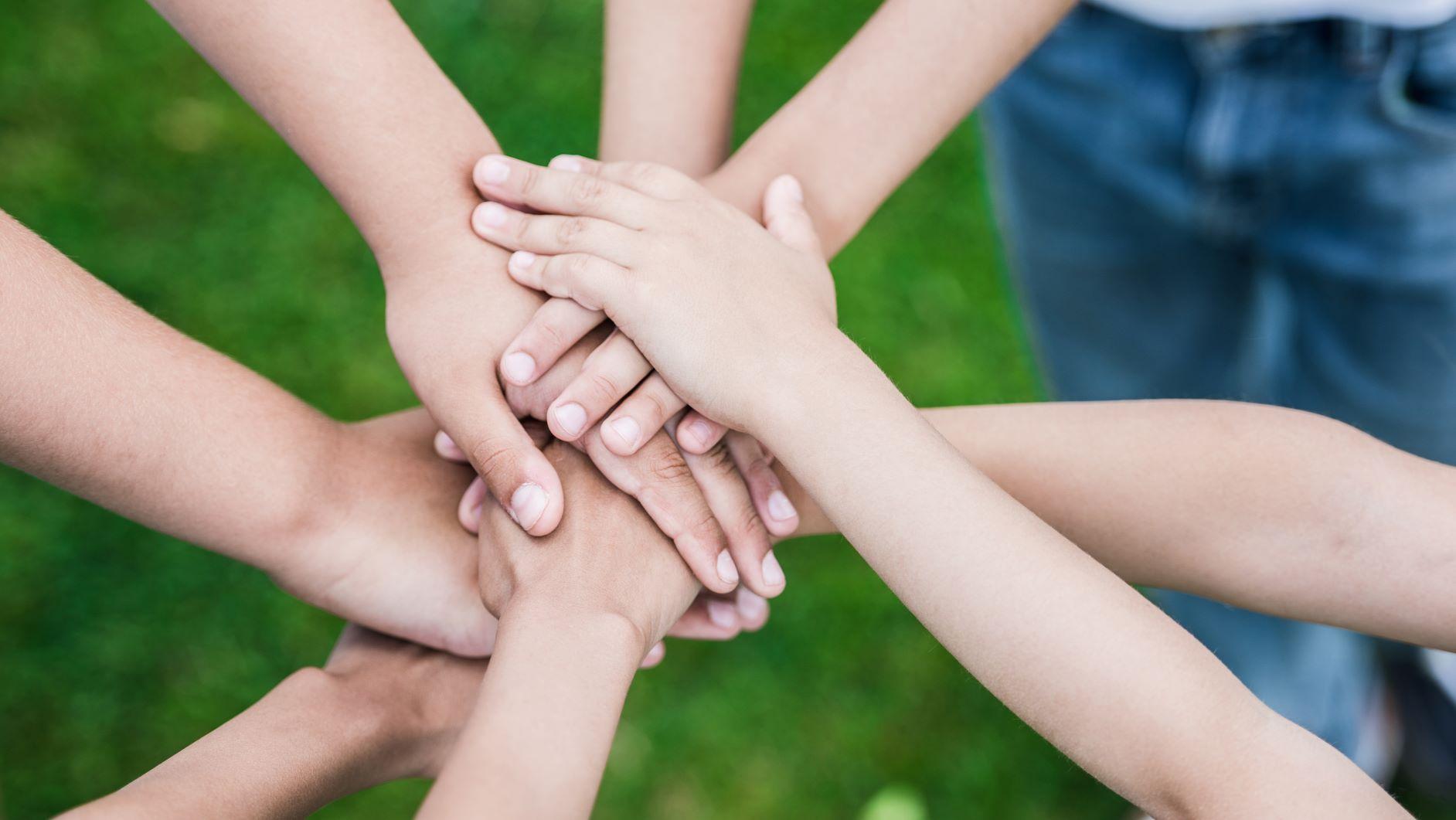 Niños apoyando su manos, en signo de colaboración pacifica