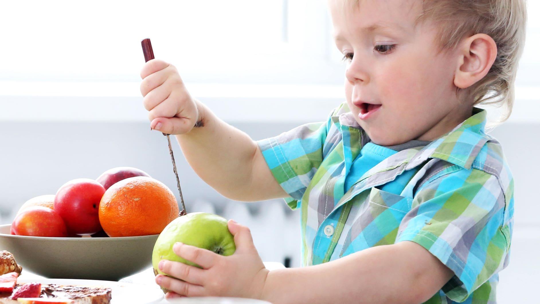 niño se esfueza por pelar una fruta sin ayuda de los adultos