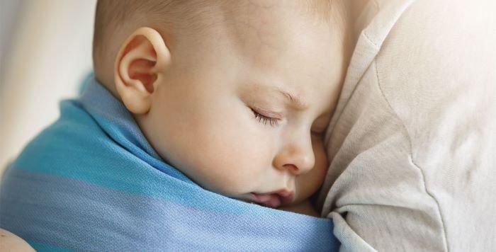 Niño durmiendo sobre el hombre de su madre