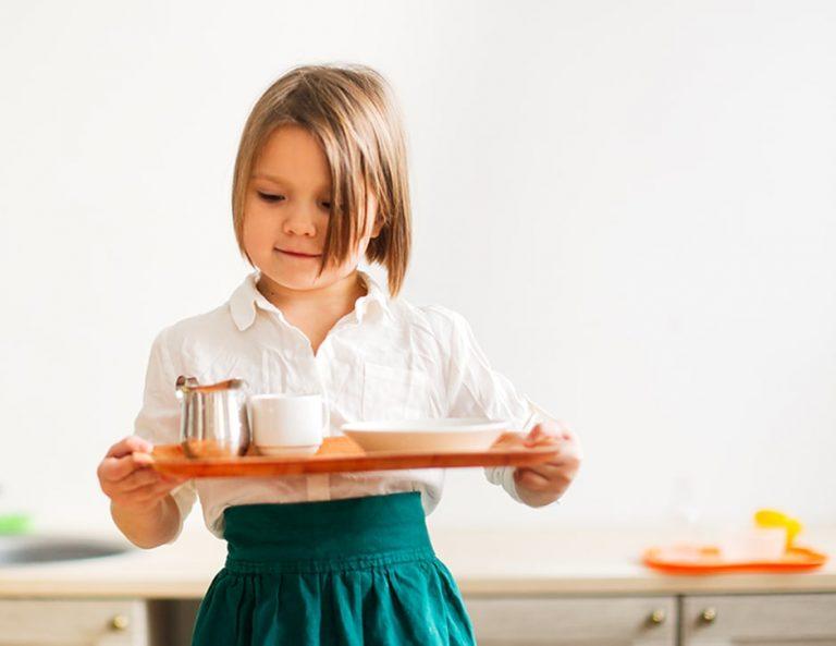 en un delantal de lino con una bandeja pone la mesa, ayudando a mamá