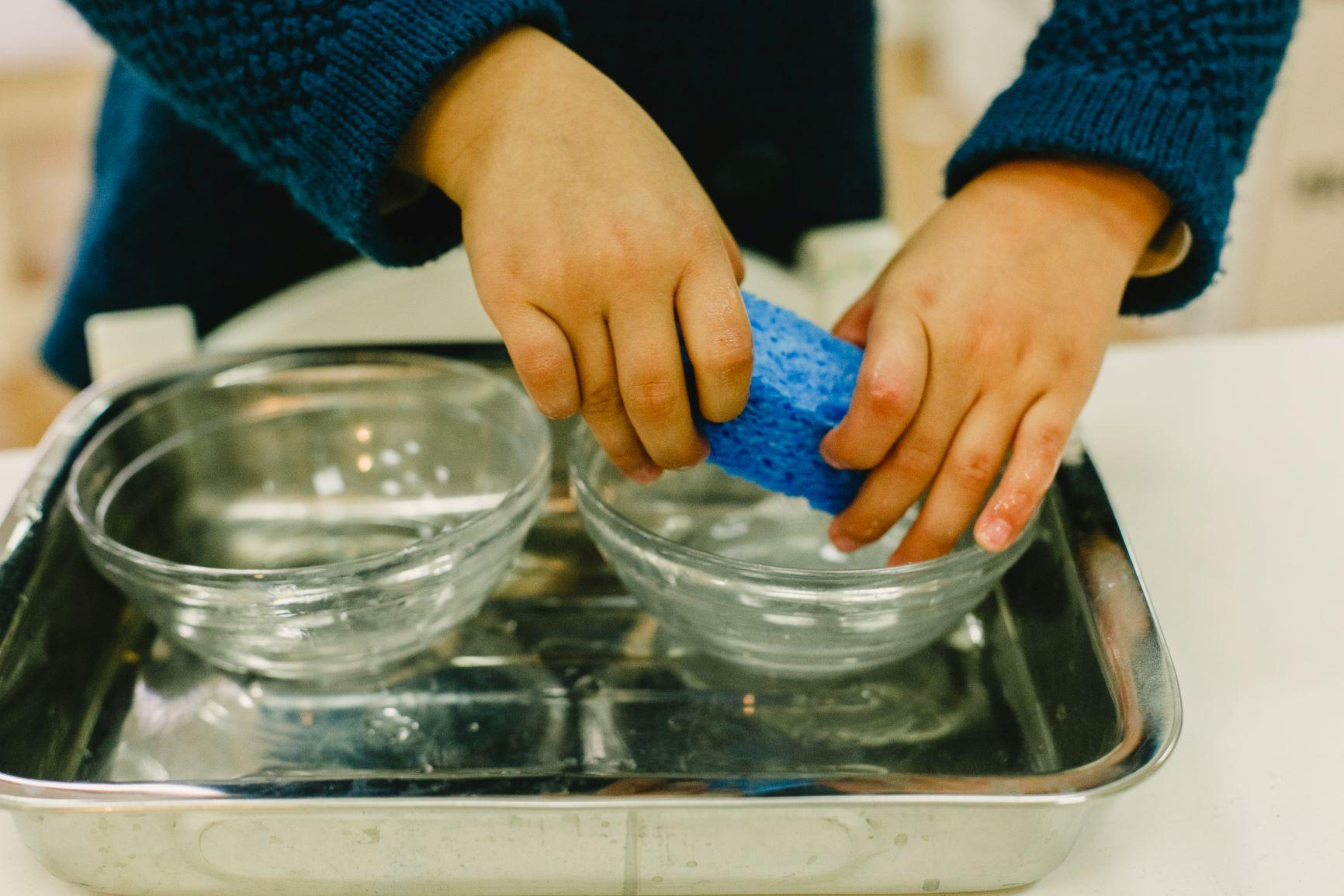 niño lavando los platos sin ayuda del asistente Montessori